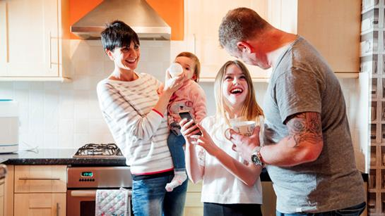 Family Laughing In Kitchen